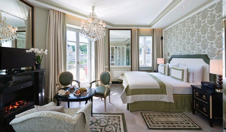 Hotel Sacher junipt suite, double bed, chairs, armchair, elegant decor, glass chandelier