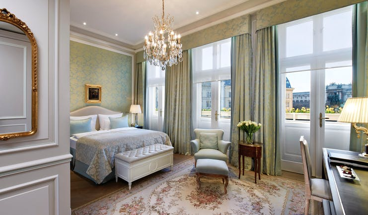Hotel Sacher Vienna deluxe bedroom ornate mirror chandelier armchair with footstool and large windows