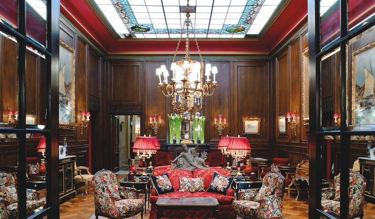 Hotel Sacher Vienna lobby seating area large glass skylight wooden walls and armchairs