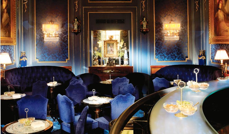 Hotel Sacher Wien Blaue Bar ornate room with a large chandelier at the centre of the room, blue chairs and sofas occupy the room with large paintings on the walls