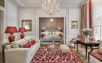 Hotel Sacher Wien Philharmoniker Suite two rooms, one ith a double ed the other with a sofa and tables with a large overhanging chandelier