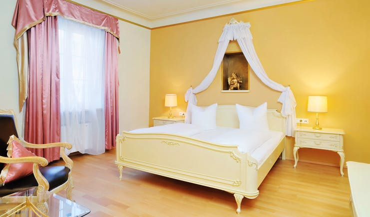Hotel Schwarzer Adler classic room, bright elegant decor, double bed with drapery