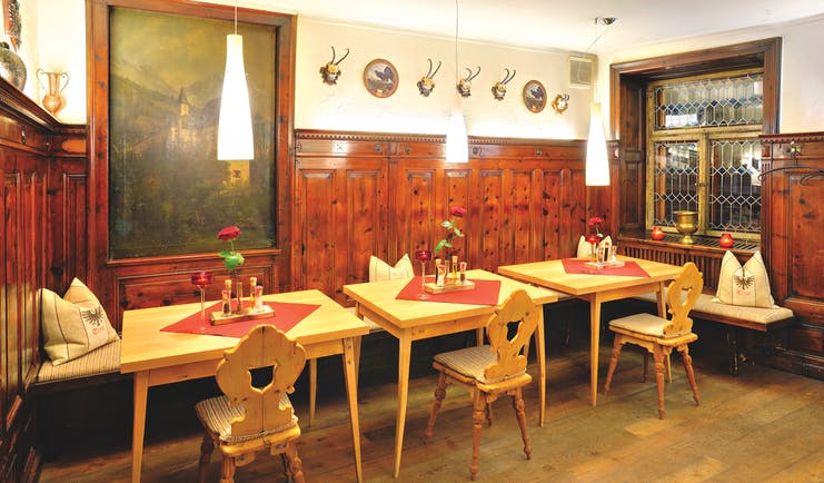 Hotel Schwarzer Adler restaurant, dining tables chairs and benches, traditional decor, wood panelling, paintings