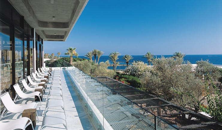 Almyra Hotel Cyprus terrace balcony with loungers overlooking trees and sea