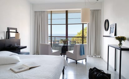 Bedroom at Almyra Hotel with balcony showing sea view, large double bed and seating area