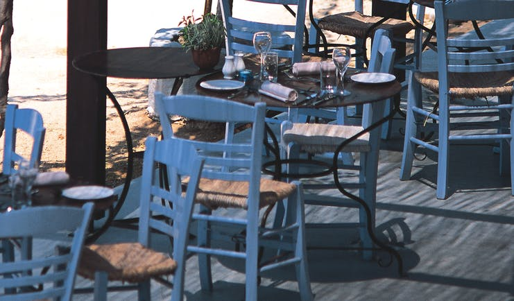 Outdoor dining terrace with white and wooden tables and chairs set out