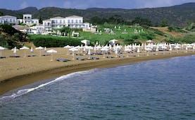 Anassa Hotel beach with white umbrellas and sunbeds