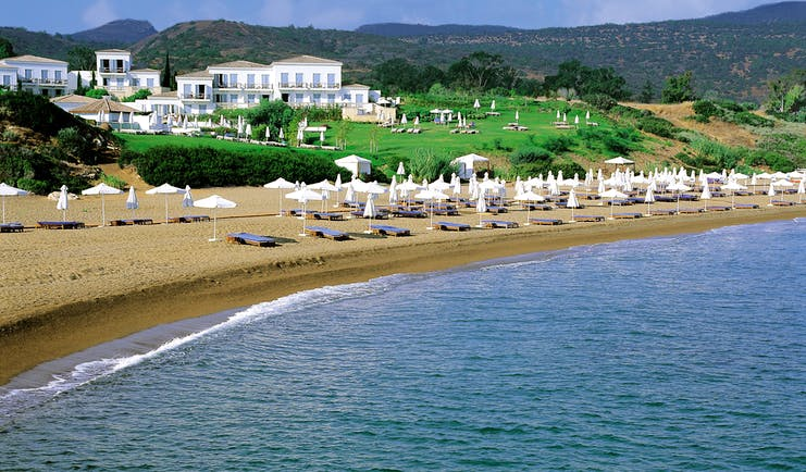 Anassa Hotel beach with white umbrellas and sunbeds