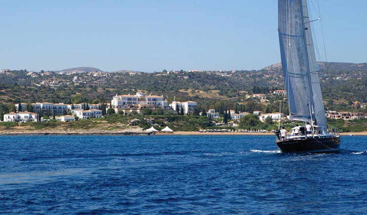 View of the Anassa Hotel from the sea with a sail boat out in front
