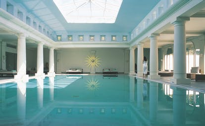 Anassa Hotel indoor pool with white pillars around the dge of the pool and a large glass ceiling
