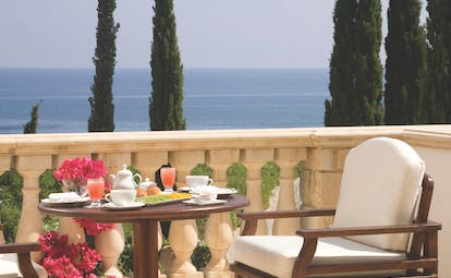 Anassa Hotel dining area on terrace balcony looking over sea