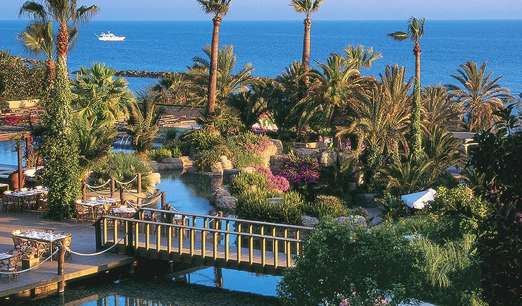 Annabelle Hotel Cyprus exterior panorama of hotel grounds with palm trees flowers and a bridge with sea views