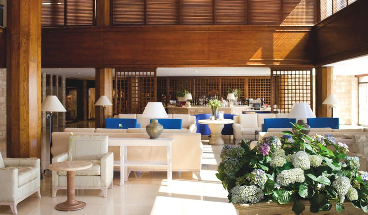 Annabelle Hotel Cyprus bar area with blue and white sofas and wooden walls and columns