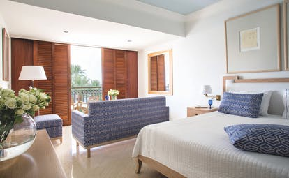 Annabelle Hotel Cyprus deluxe suite sea bedroom blue and white sofa and wooden doors to a balcony
