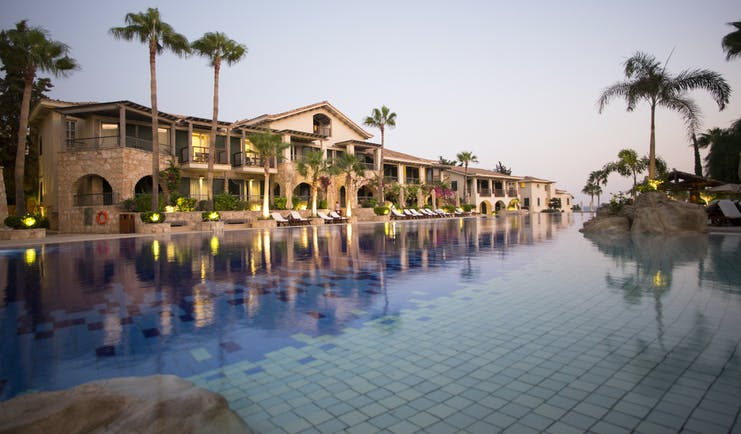 Columbia Beach Resort Cyprus outdoor pool and large building with palm trees and arches