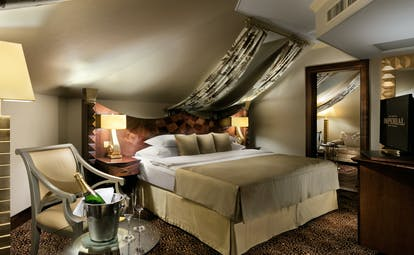 Executive suite with large double bed, arm chair, a television and lamp shades