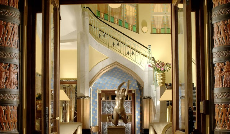 Entrance to hotel with high ceiling, large chandelier and statues