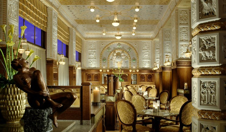 Art Deco Imperial resturant, grand lavish decor, statues, carved walls and columns, tables and chairs