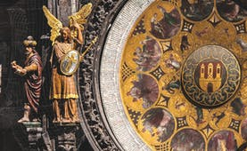Intricate and ornate detail of an astronomical clock in gold with tiny figures including an angel Prague