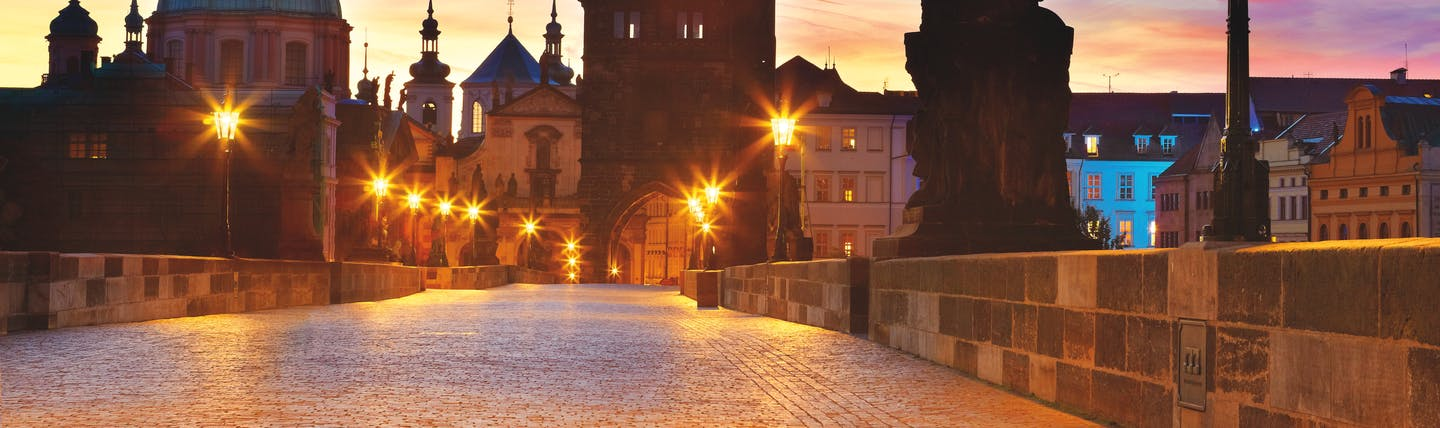 Evening sky with lights and the towers of the bridge and buildings standing out on Charles Bridge Prague
