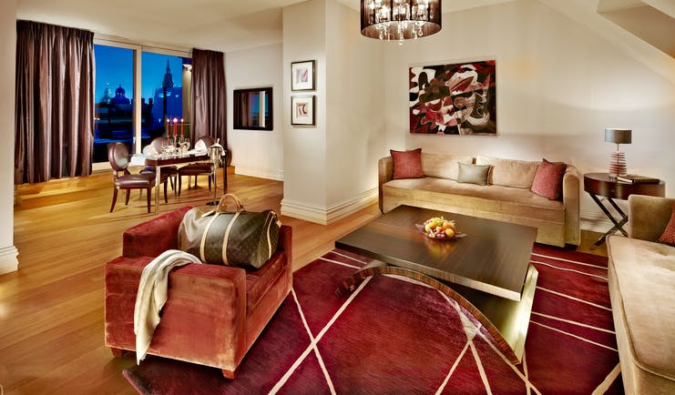 Grand Mark Prague Bohemia suite lounge area, armchairs and sofa, table and chairs, large windows with city views, colourful decor