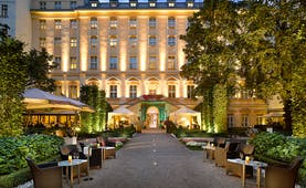 Grand Mark Prague exterior, hotel building, walkway to entrance with lawned gardens on each side, outdoor seating area