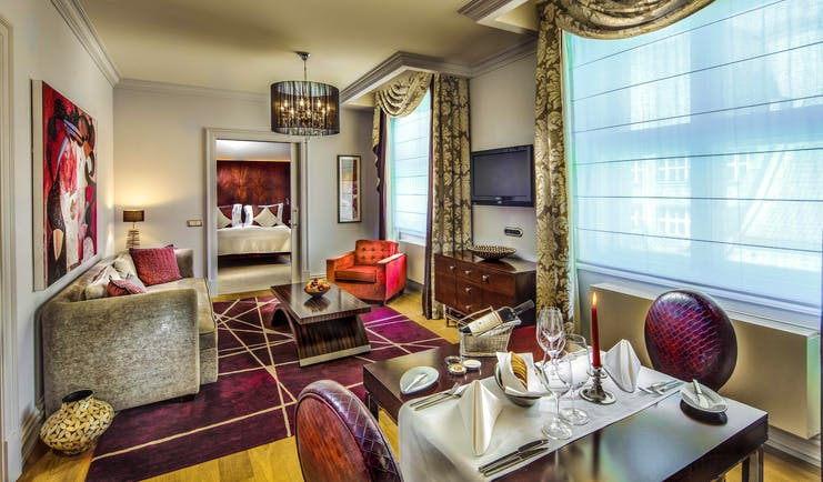 Grand Mark Prague family suite living area, tables and chairs, sofa, bedroom through door, colourful modern decor