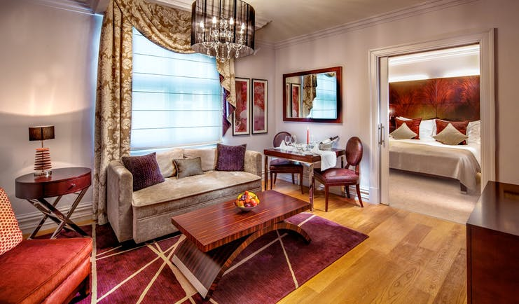 Grand deluxe room with large bed, sofa chandelier and coffee table