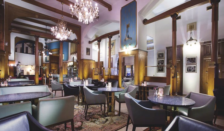 Hotel Paris Prague cafe large room with wooden beams and panels chandeliers and several chairs