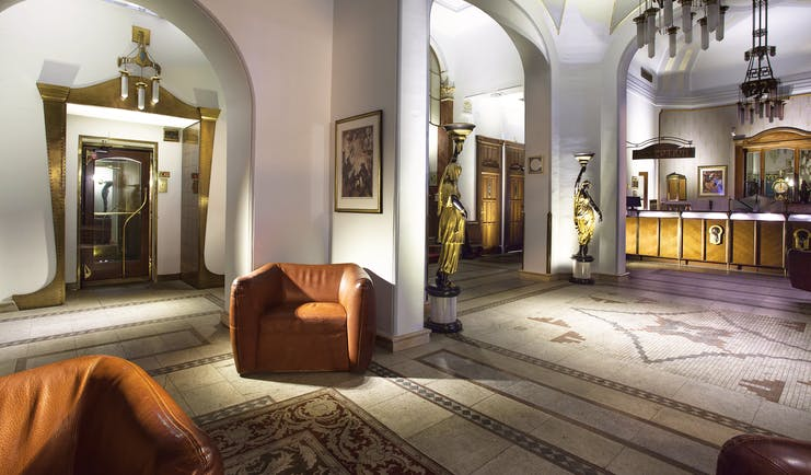 Hotel Paris Prague lobby area  archways mosaic floors chairs and two statue lamps