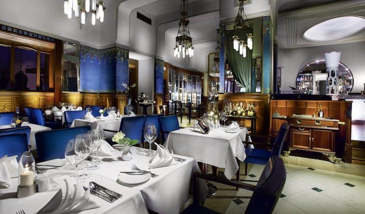 Hotel Paris Prague restaurant Sarah Bernhardt  indoor dining area with wooden panelled walls and chandeliers