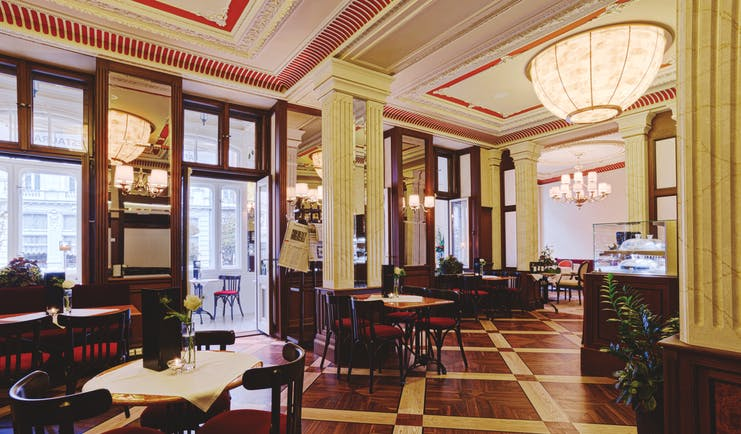 Hotel Quisisana Palace Karlovy Vary restaurant dining room wood panelling wooden floors large windows and ornate ceiling