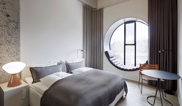 Hotel Ottilia superior room, double bed, round window with window seat, scandinavian decor