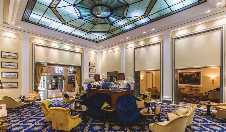 Excelsior Hotel Ernest Cologne winter garden stained glass ceiling blue sofas and cream chairs and tables