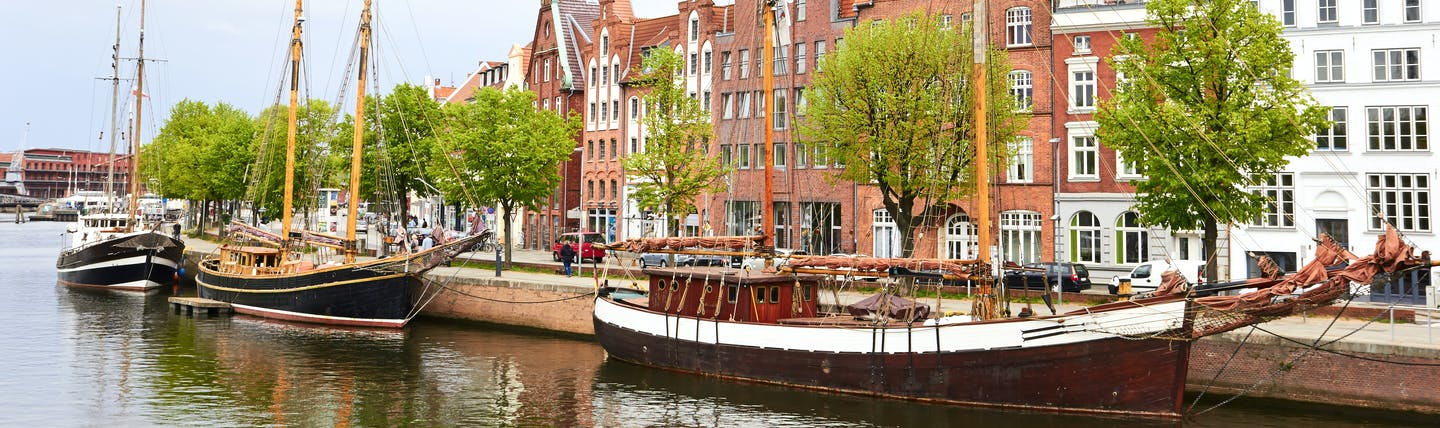 Wooden boats moored on river by old warehouses in Lubeck