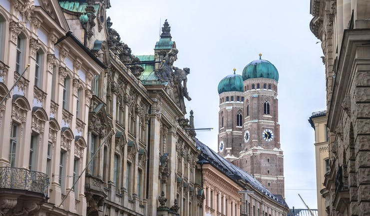 Church towers with green roof and grey stone tall buildings in Munich