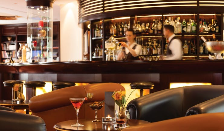 Bar and sitting area at the Hotel Bulow Palais with wooden pannels, a wooden bar and leather arm chairs