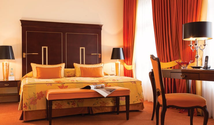 Deluxe double room at the Hotel Bulow Palais with an orange colour scheme, large double bed, red curtains and wooden bed frame