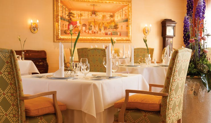 Restaurant dining area at the Hotel Bulow Palais with tables set up around the room and paintings on the walls