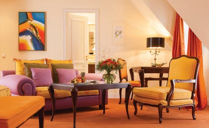 Junior suite at the Hotel Bulow Palais with an orange colour scheme, sofa, arm chair and double bed