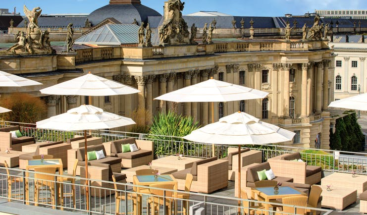 Hotel de Rome Berlin rooftop terrace with sofas and umbrellas overlooking large building overlooking the opera house