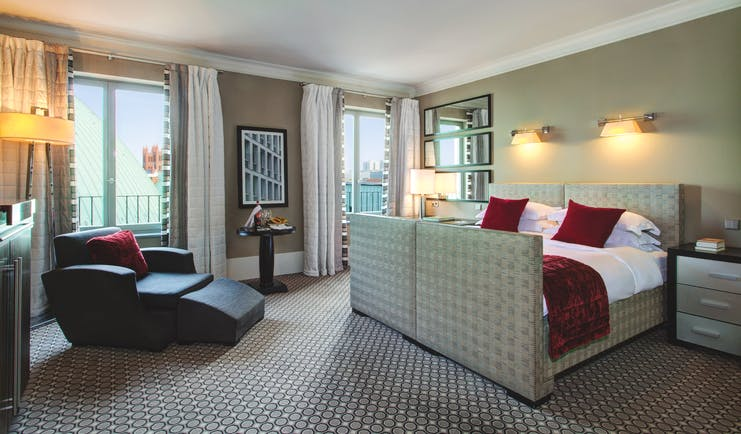 Hotel de Rome deluxe bedroom grey head board and foot board reclining armchair and large windows