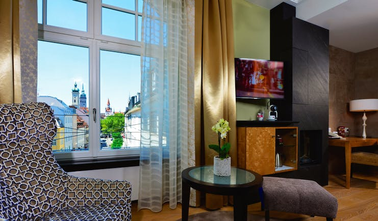 Hotel Torbrau Munich junior suite armchair table desk and telephone window with a city view
