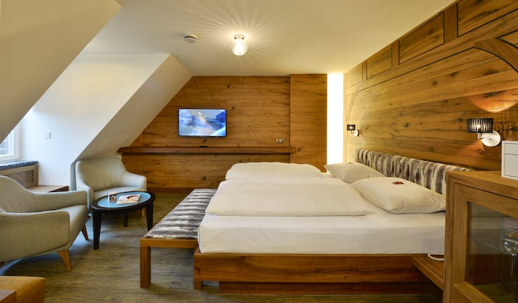 Hotel Torbrau Munich bedroom with wooden walls skylight window and two cream chairs
