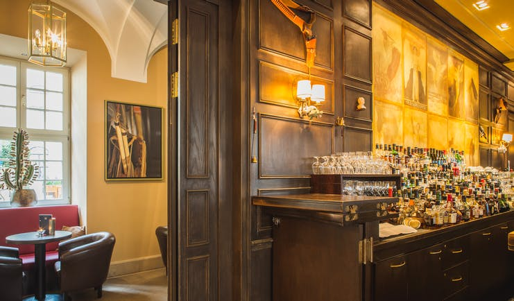 Taschenbergpalais bar, leather armchairs, wood panelling, bar filled with bottles, traditional decor