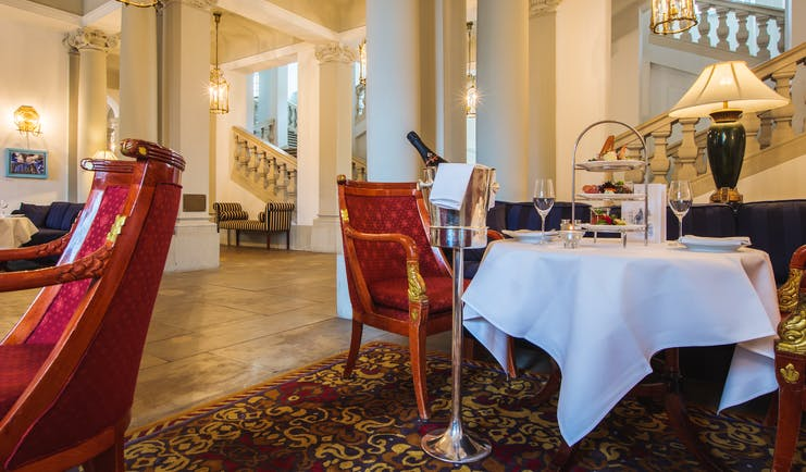 Taschenbergpalais cafe vestibul, indoor eating area, grand decor woth stone pilars and carbed staircase, table and chairs