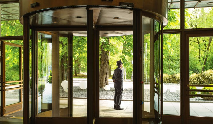 Revolving entrance doors to the hotel with butler standing outside to greet guests