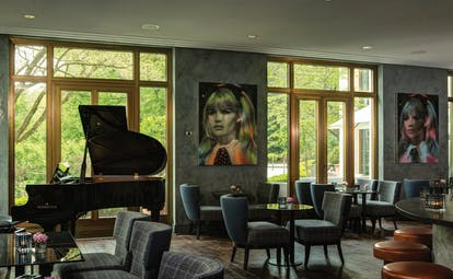 Lounge area at the Charles Hotel with seating areas set up, a piano in the corner and modern pieces of art on the wall