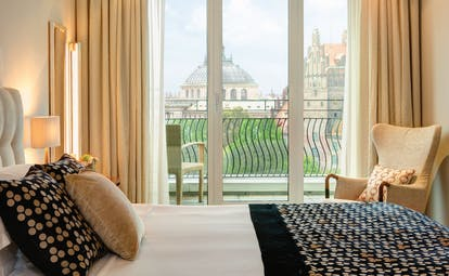 Monforte suite at the Charles Hotel with a large double bed, bifolding doors leading on to a balcony overlooking the city