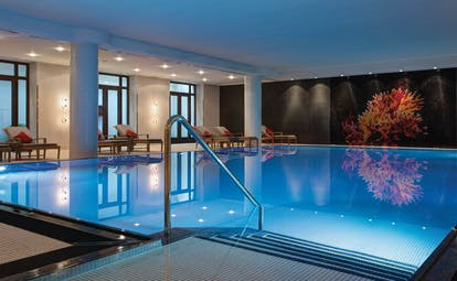 Pool and spa at the Charles Hotel Munich with steps leading into a pool with little lights lighting up the bottom